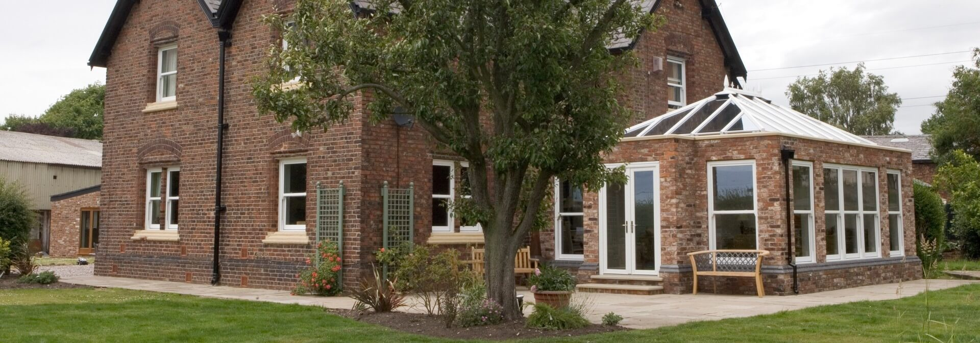 A brick orangery extension with glass roof installed onto large property
